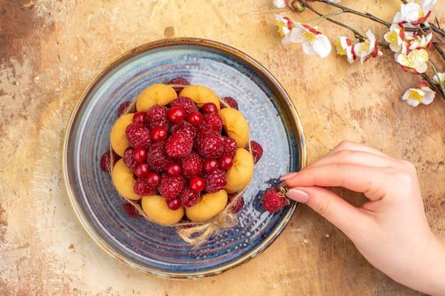 Oben ansicht von händen, die eine erdbeere auf frisch gebackenem weichem kuchen mit früchten auf mischfarbtabelle halten