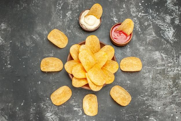 Oben ansicht von hausgemachten kartoffelchips, die in einem kreis und mayonnaise-ketchup auf grauem tisch angeordnet sind