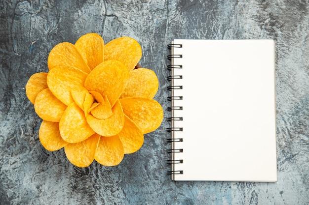 Oben ansicht von kartoffelchips, die wie eine blume verziert sind, die in einer braunen schüssel und einem notizbuch auf grauem tisch geformt wird