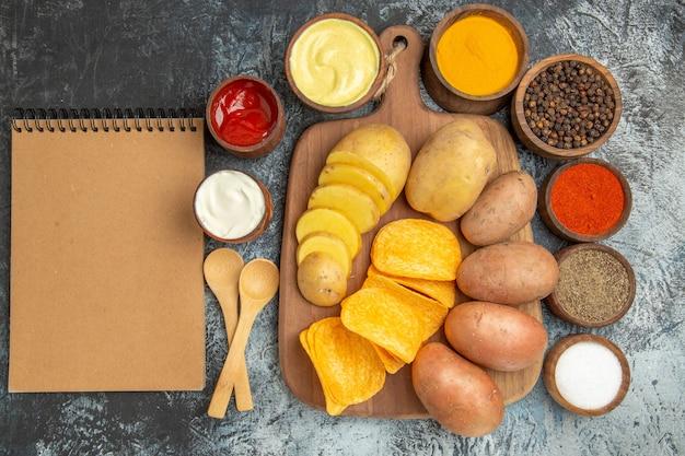 Oben ansicht von knusprigen pommes und ungekochten kartoffeln auf holzschneidebrett verschiedene gewürze und notizbuch auf grauem tisch
