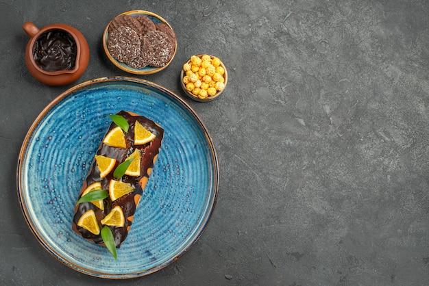 Oben ansicht von köstlichen kuchen auf blauem tablett und keksen auf dunklem tisch
