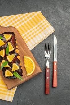 Oben ansicht von köstlichen weichen kuchen auf holzbrett und geschnittenen orangen mit blättern auf dunklem tisch