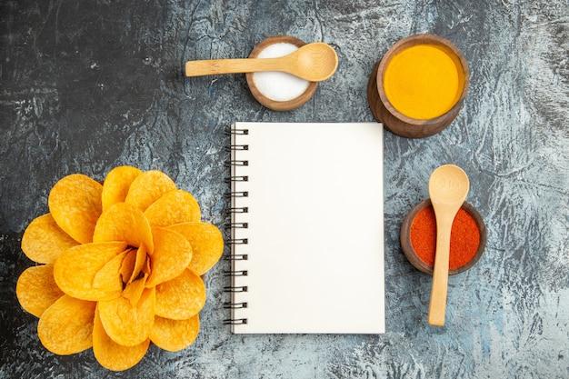 Oben ansicht von leckeren kartoffelchips, die wie blumen gewürzt sind, verschiedene gewürze mit löffeln darauf und notizbuch auf grauem tisch