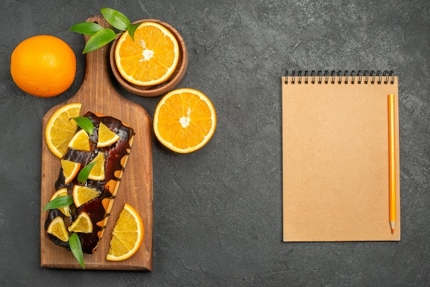 Oben ansicht von leckeren kuchen ganz und geschnittene orangen auf schneidebrett neben notizbuch auf schwarzem tisch