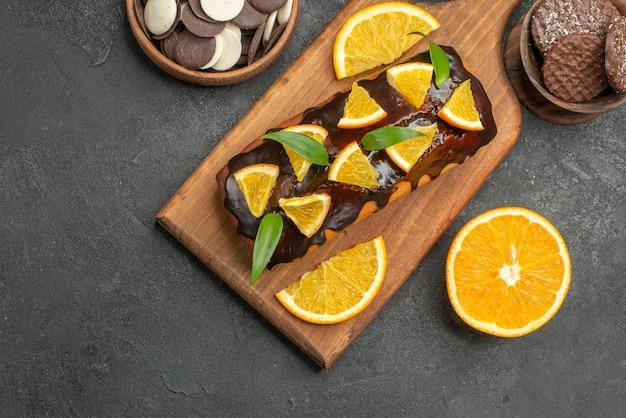 Oben ansicht von leckeren kuchen schneiden zitronen mit keksen auf schneidebrett auf dunklem backboden