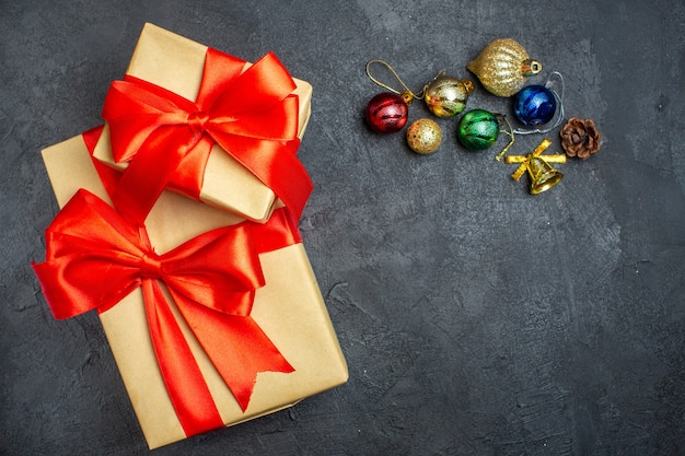 Oben ansicht von schönen geschenken mit bogenförmigem banddekorationszubehör auf einem dunklen hintergrund