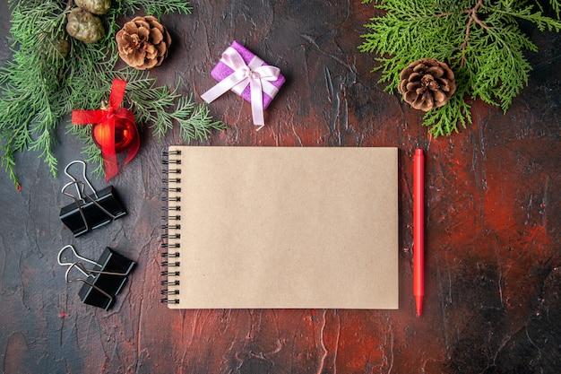 Oben ansicht von tannenzweigen dekorationszubehör und geschenk neben notizbuch mit stift auf dunklem hintergrund