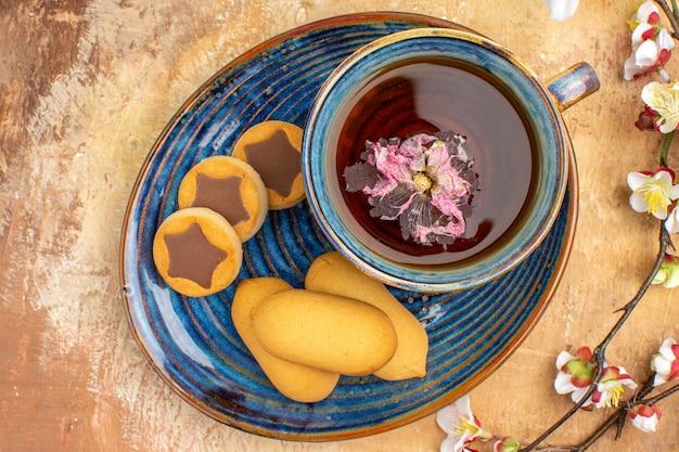 Oben ansicht von verschiedenen keksen eine tasse tee und blumen auf gemischtem farbtisch