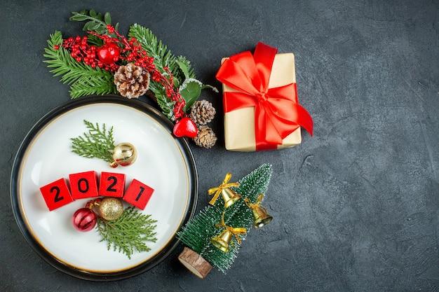 Oben ansicht von zahlen dekorationszubehör auf einem teller tannenzweige nadelbaumkegel weihnachtsbaum auf dunklem tisch