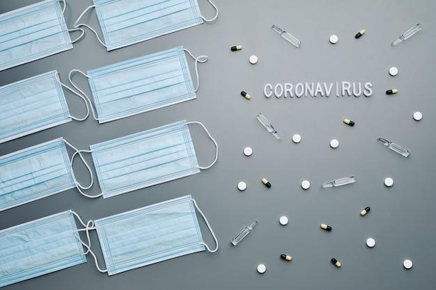 Oben ansicht zusammensetzung der medizinischen masken mit coronavirus-wort und medikamenten, die im muster über grauem hintergrund angeordnet sind,