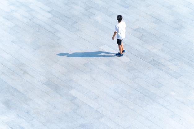 Oben auf der luftaufnahme eines jungen, der auf dem fußgängerweg im freien zum reisen oder trainieren geht?