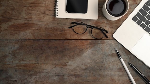 Oben blick auf computer-laptop, kaffeetasse, smartphone, brille und notebook auf holztisch.