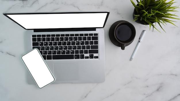 Oben blick auf computer-laptop und smartphone mit leerem bildschirm auf marmorhintergrund.