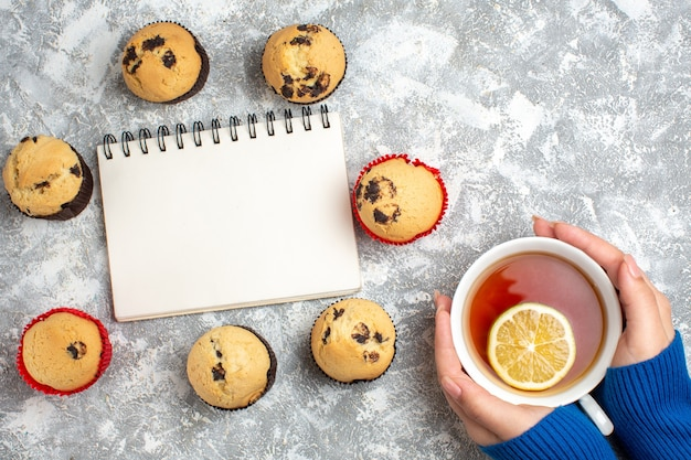 Oben blick auf das geschlossene notizbuch zwischen köstlichen kleinen cupcakes mit schokolade und hand, die eine tasse schwarzen tee mit zitrone auf eisoberfläche hält holding