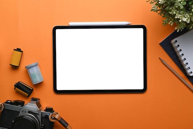 Oben blick auf den arbeitsplatz des fotografen mit digitalem tablet, kamera, notebook und zimmerpflanze auf orangem hintergrund.