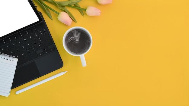 Oben blick auf den designer-arbeitsplatz mit computertablette, kaffeetasse, notizbuch, stylus-stift und kopienraum auf gelbem hintergrund.