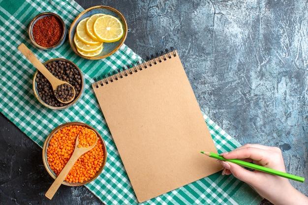 Oben blick auf den hintergrund des abendessens mit verschiedenen gewürzen, gelbe erbse und hand, die einen stift auf einem spiralnotizbuch auf dunklem tisch hält