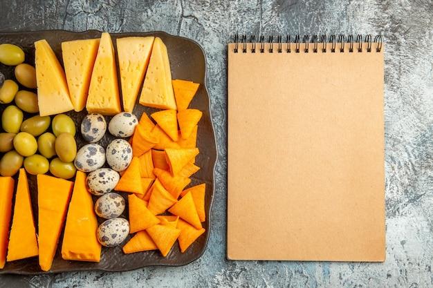 Oben blick auf den köstlichen besten snack für wein auf braunem tablett und notizbuch auf eishintergrund