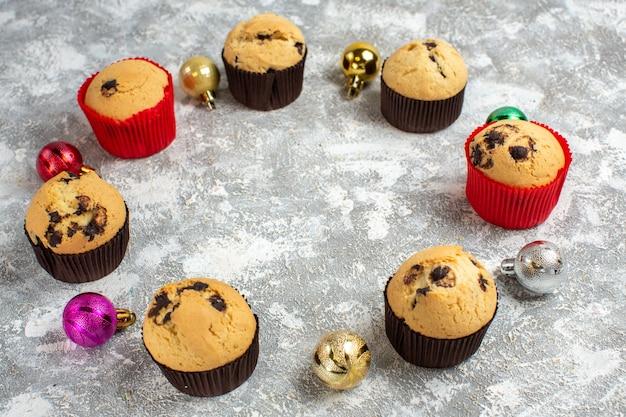 Oben blick auf den leeren raum zwischen frisch gebackenen leckeren kleinen cupcakes und dekorationszubehör auf dem eistisch