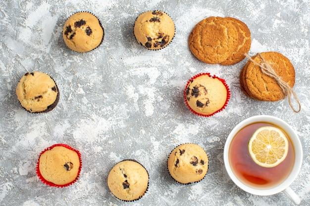 Oben blick auf den leeren raum zwischen köstlichen kleinen cupcakes mit schokolade und einer tasse schwarzem tee mit zitronenplätzchen auf eisfläche
