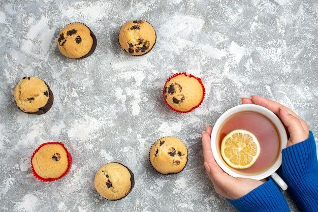 Oben blick auf den leeren raum zwischen köstlichen kleinen cupcakes mit schokolade und hand, die eine tasse schwarzen tee mit zitrone auf eisoberfläche hält