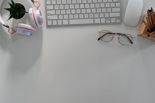 Oben blick auf den schreibtisch mit tastatur, brille, kopfhörer und kopienraum auf weißem hintergrund.