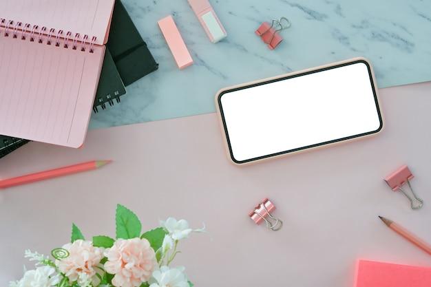 Oben blick auf den weiblichen arbeitsplatz mit smartphone und büromaterial auf rosa und marmor