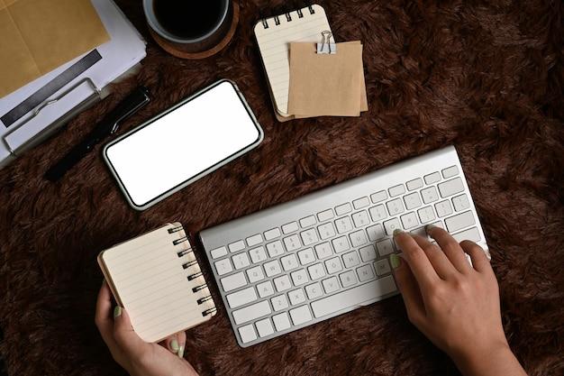 Oben blick auf die frau, die auf der drahtlosen tastatur tippt und das notebook über einem braunen pelzteppich hält.