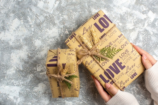 Oben blick auf die hand, die ein schönes verpacktes geschenk für weihnachten auf der eisoberfläche hält