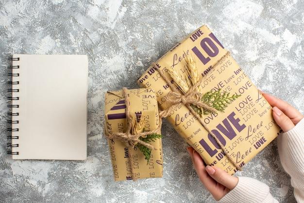 Oben blick auf die hand, die ein schönes verpacktes geschenk für weihnachten und ein geschlossenes notizbuch auf der eisoberfläche hält