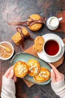 Oben blick auf die hand, die ein tablett mit frischen pfannkuchen nimmt, eine tasse schwarzen tee auf einem holzschneidebrett honig gestapelte keksmilch auf einer dunklen oberfläche