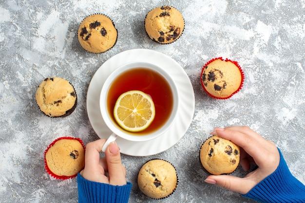 Oben blick auf die hand, die eine tasse tee und einen der köstlichen kleinen cupcakes mit schokolade auf der eisoberfläche hält