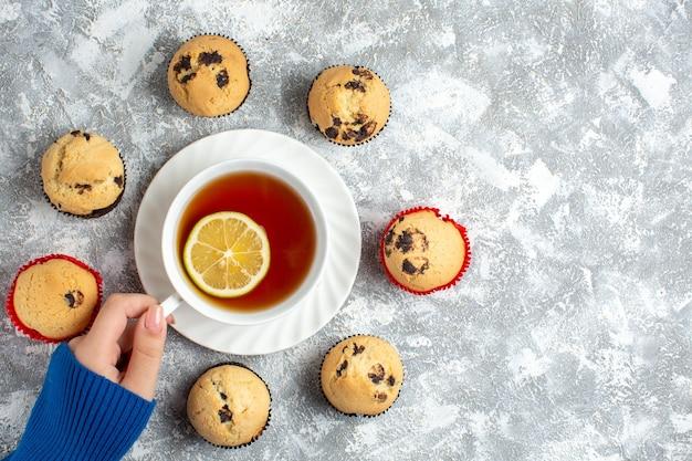 Oben blick auf die hand, die eine tasse tee und köstliche kleine cupcakes mit schokolade auf der eisoberfläche hält