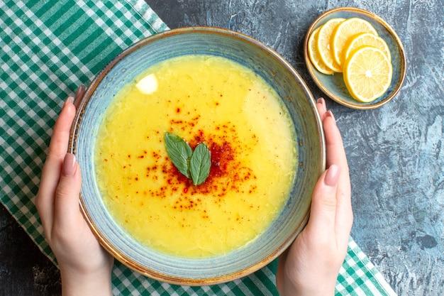 Oben blick auf die hand, die einen blauen topf mit leckerer suppe hält, serviert mit minze und pfeffer served