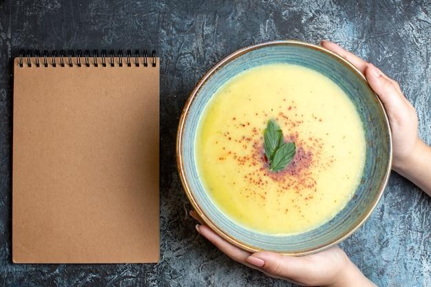 Oben blick auf die hand, die einen blauen topf mit leckerer suppe und spiralnotizbuch auf blauem hintergrund hält