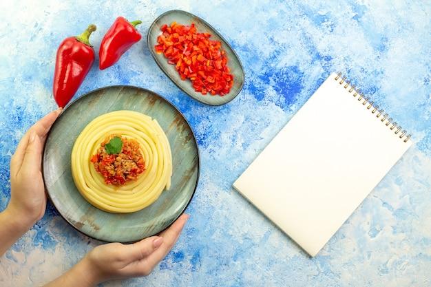 Oben blick auf die hand, die einen grauen teller mit köstlichen gehackten spagetti und ganzer roter paprika neben einem spiralnotizbuch auf blauem tisch hält