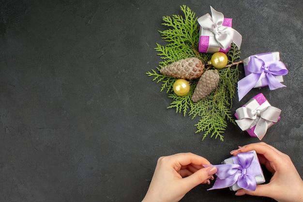 Oben blick auf die hand, die eines der bunten geschenke und dekorationszubehör auf dunklem hintergrund hält