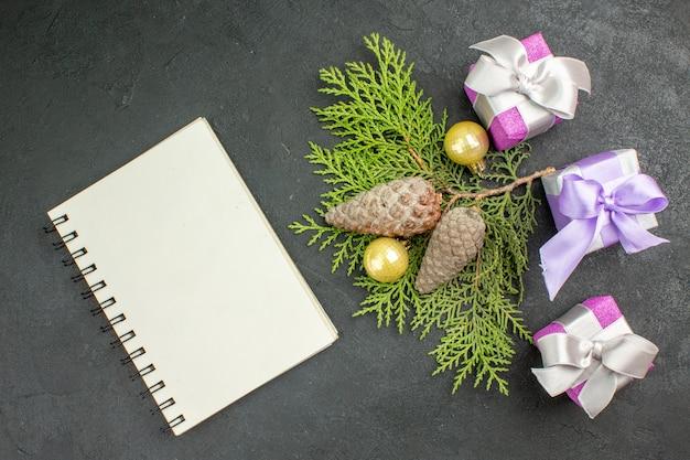 Oben blick auf die hand, die eines von bunten geschenken und dekorationszubehör und spiralnotizbuch auf dunklem hintergrund hält