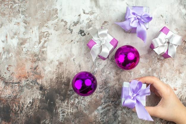 Oben blick auf die hand, die eines von drei weihnachtsgeschenken für familienmitglieder und ein dekorationszubehör auf der linken seite auf eishintergrund hält