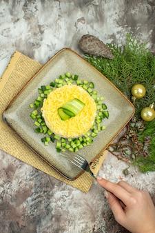 Oben blick auf die hand, die gabel auf leckerem salat hält, serviert mit gehackter gurke und messergabel auf einer alten zeitung