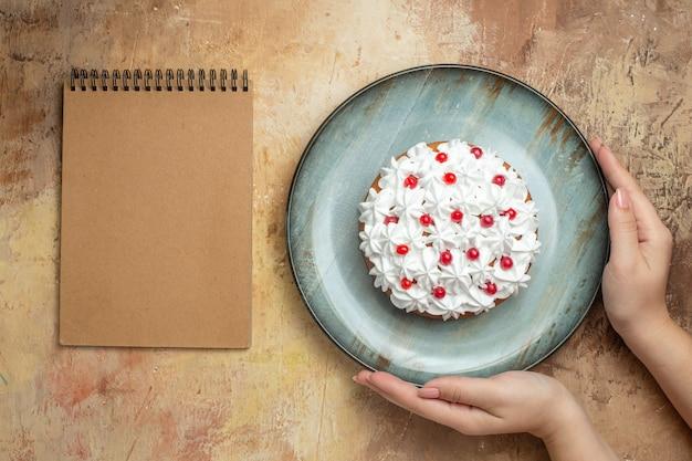 Oben blick auf die hand, die leckeren kuchen hält, der mit sahne und johannisbeere auf einem blauen teller und einem spiralnotizbuch auf einem bunten tisch dekoriert ist