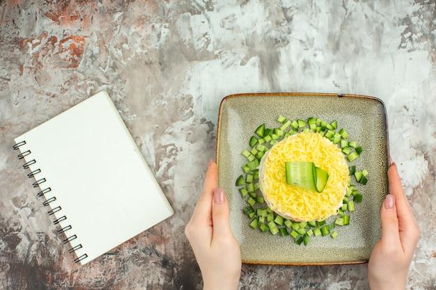 Oben blick auf die hand, die leckeren salat hält, serviert mit gehackter gurke und notizbuch auf gemischtem farbhintergrund