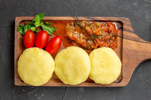 Oben blick auf die zubereitung des abendessens mit ungekochtem gemüse auf einem braunen schneidebrett