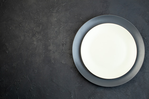 Oben blick auf dunkle farbe und weiße leere teller in verschiedenen größen auf schwarzem hintergrund