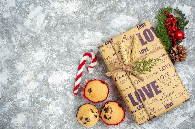 Oben blick auf ein schönes weihnachtsgeschenk mit liebesaufschrift und kleinen cupcakes tannenzweigen dekorationszubehör nadelbaumkegel auf eisoberfläche