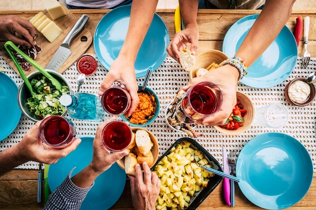 Oben blick auf eine gruppe von freunden, die zusammen essen und trinken, feiern und spaß beim toasten mit rotwein haben - farbiger tisch und dekoration - sozialer kontakt und normale lebensszene mit der familie