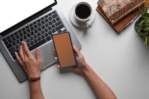 Oben blick auf eine junge frau, die an einem laptop arbeitet und ein smartphone an ihrem schreibtisch hält.