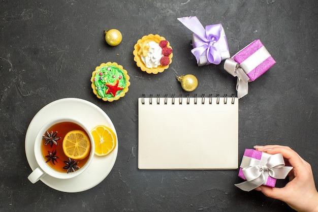 Oben blick auf eine tasse schwarzen tee mit zitrone, serviert mit keksen, notebbok und geschenken auf dunklem hintergrund