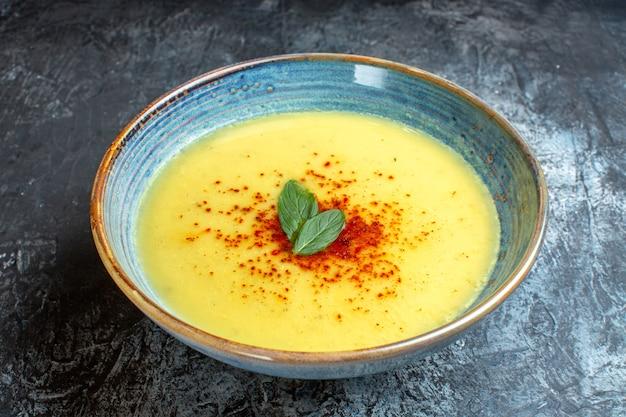 Oben blick auf einen blauen topf mit leckerer suppe, serviert mit minze auf blauem tisch