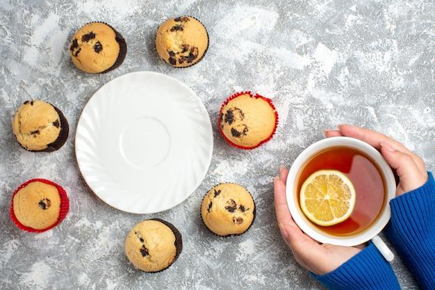 Oben blick auf einen leeren weißen teller zwischen köstlichen kleinen cupcakes mit schokolade und hand, die eine tasse schwarzen tee mit zitrone auf eisoberfläche hält